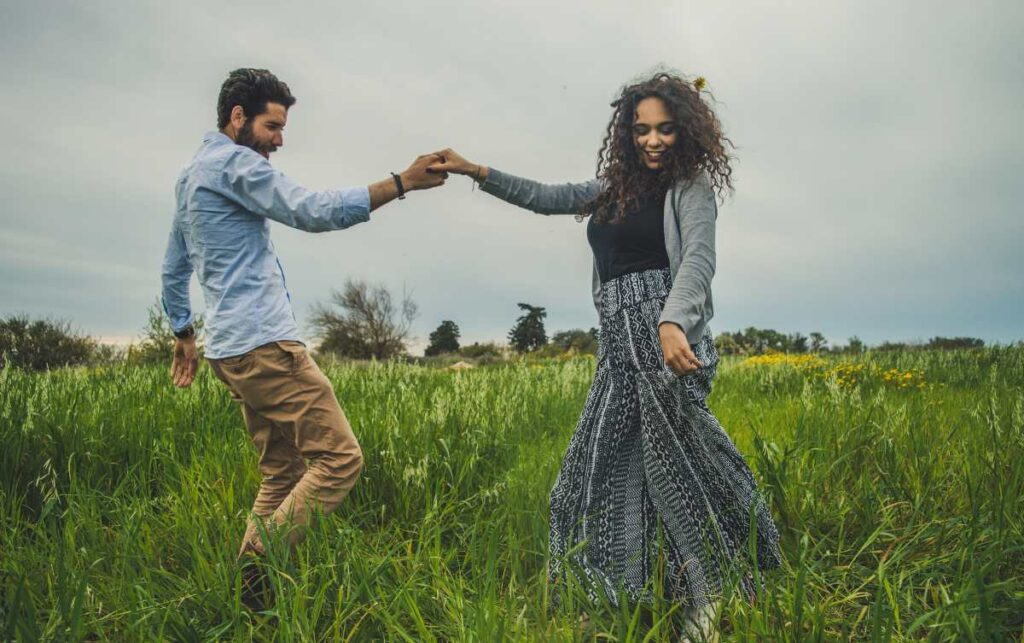 Dancing couple in a grass on a sunny day - Signs she is madly in love with you
