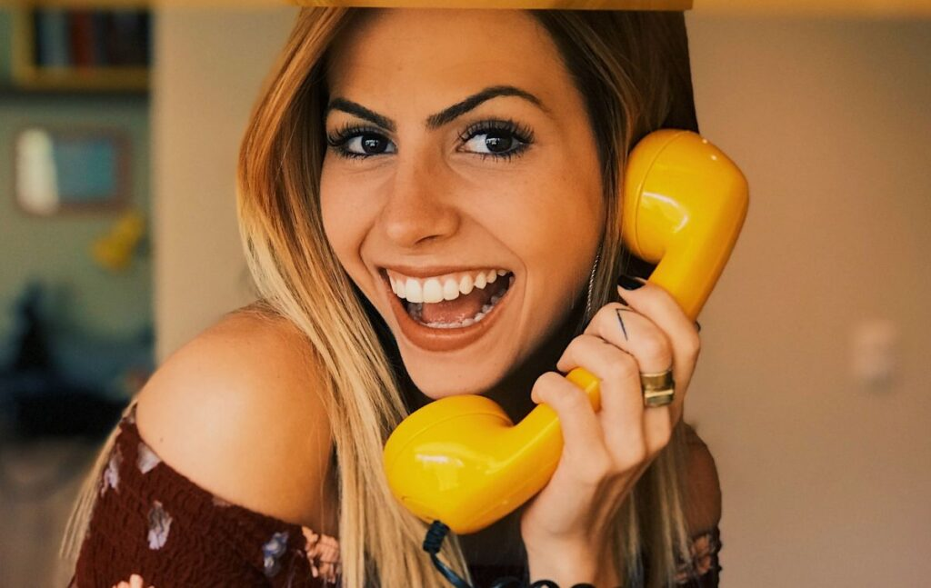 Girl holding a phone with the big smile on her face - Signs she is madly in love with you