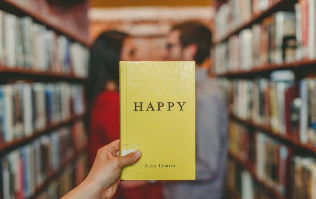 """Yellow """"Happy"""" book in front of couple who looks each other in the eyes-love at first sight quotes"""