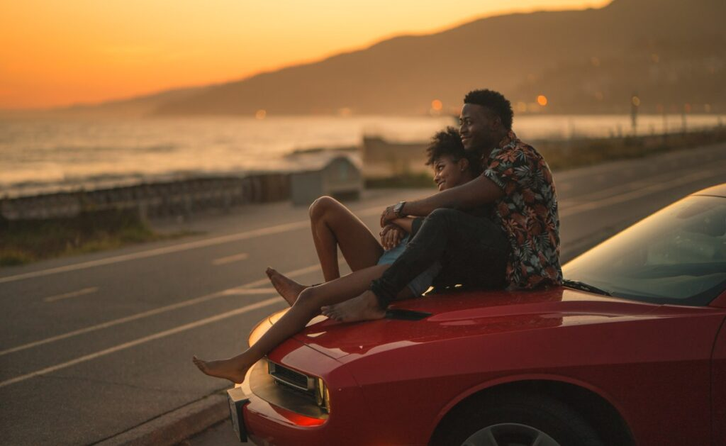 Couple sitting on a car watching sunset, date - how to ask a girl out over text